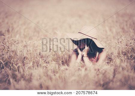 Young woman in bikini and sunhat posing in filed