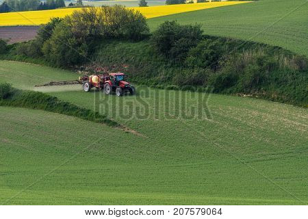 Tractor irrigate a field in South Moravia at sunset beautiful view with yellow flowers yellow field and green grass Czech Republic. Agricultural landscape