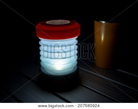 Fold up LED camping light and orange drinking mug standing on aluminium camping table in darkness, Travel, Africa.