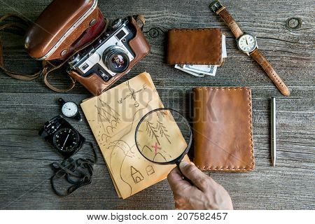 Personal travelers accessories: camera, notebook, purse, wristwatch, compass, magnifier, pen, money, map. Vintage background.