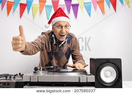 Elderly man with a christmas hat playing music on a turntable and making a thumb up sign against a wall with decoration flags