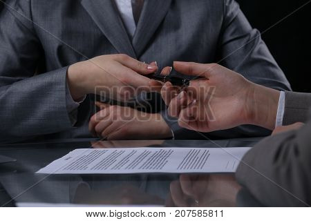 Group of businesspeople or lawyers at meeting. Signing contract concept. Close-up of human hands at work. Low key lighting.