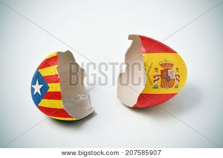 the two halves of a cracked eggshell, one patterned with the Estelada, the Catalan pro-independence flag and the other one patterned with the flag of Spain