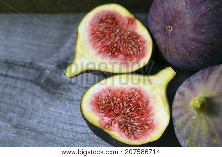 Fresh ripe fig fruits on old wooden background.Whole and sliced figs.Selective focus.