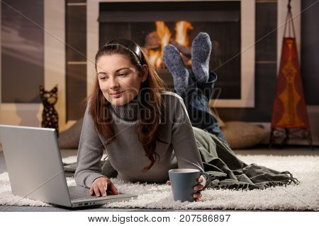 Young woman lying on front at fireplace on a winter day, using laptop, smiling.
