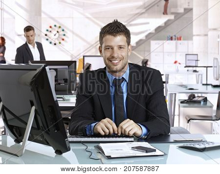 Happy young rookie caucasian businessman at business office with computer, sitting behind desk, smiling, looking at camera, suit and tie.