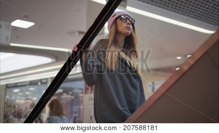 Stylish woman hipster going up escalator in a mall