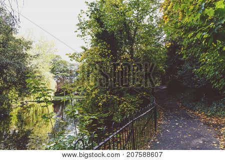 DUBLIN IRELAND - September 30th 2017: Detail of St Stephen's Green park near the pond with early autumn tones (unidentified people in the distance)