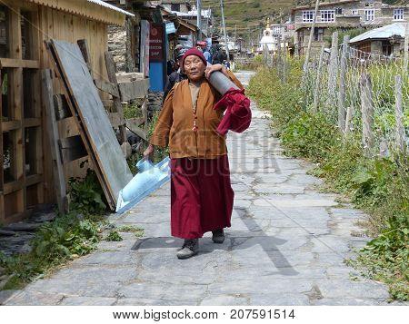 Manang Nepal september 13 2015: Nepalese monk woman carries toilet bowl in Manang village - Meeting local people during Annapurna Circuit trek in Nepal
