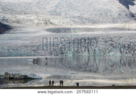 Several people contemplate Ice Lagoon Fjallsarlon. Glacier of this lagoon is just a short distance away view point.
