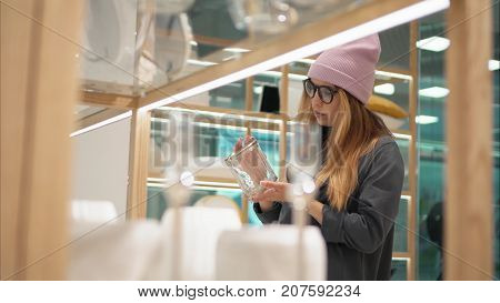 A young hipster female in fashion glasses chooses home accessories in the store