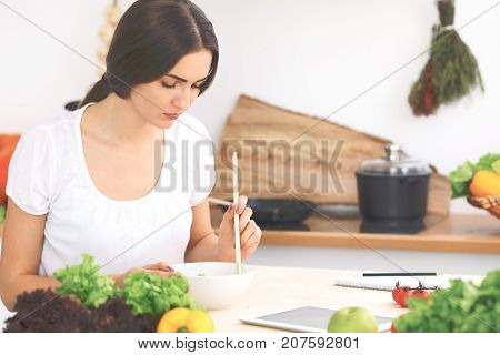 Beautiful  Hispanic or latin american woman is holding wooden spoon while cooking in the kitchen. Brunette housewife searching new recipe by touch pad computer.
