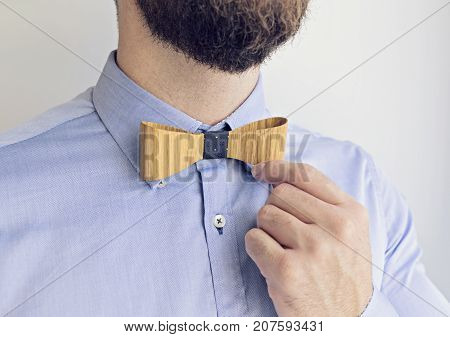 Adult Bearded Man Businessman is Going to Work or on Date. He adjusts Hand Bow Tie Happy Boss's day concept, copy space, selective focus