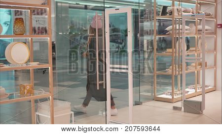 A young hipster female in fashion glasses leaves the store
