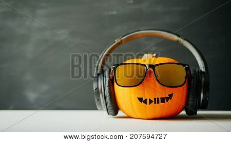 Pumpkin for Halloween in the form of a head with a smile in glasses and headphones. Play music for Halloween. Playlist.