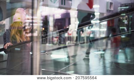 A young stylish hipster woman climbs a trevalator in a store. Shopping