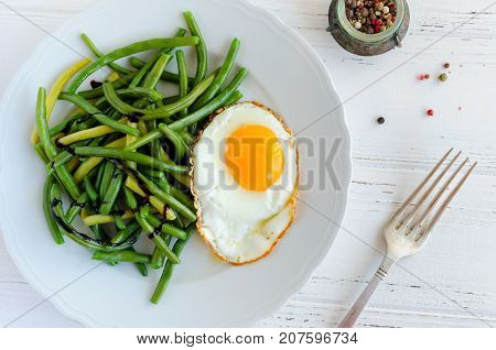 Cooked green beans with sauce balsamico glassa and fried egg in white plate on wooden background with fork. Healthy vegetarian food concept. Top view.