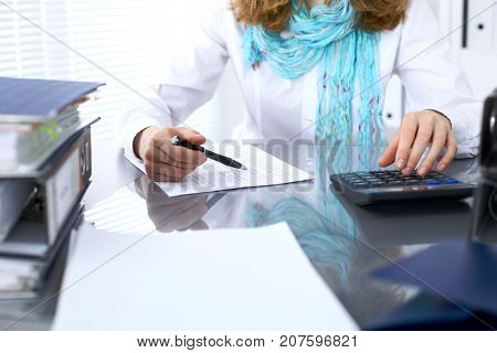 Female bookkeeper or financial inspector  making report, calculating or checking balance. Internal Revenue Service checking financial document. Audit concept.