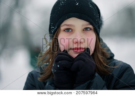 Teen girl froze. The child warms hands clasped to his face. Portrait of a beautiful girl. Girl in black clothes