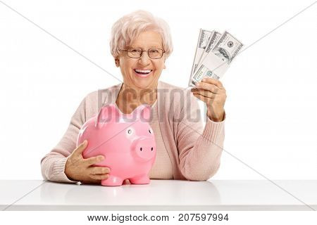 Happy elderly woman with a piggybank and money bundles seated at a table isolated on white background