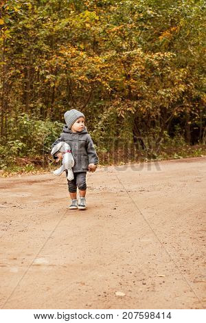 scared lost boy walking and looking people in the forest in a gray coat with a toy rabbit and mushroom in his hand