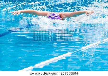 fast swimmer boy swimming in Butterfly stroke with both arm stretching out wide good for working hard or sport concept with room for text or copy space at bottom