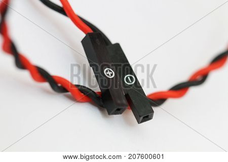 close-up cable wire with connection for electronic devices on white background. Black wire for negative and Red wire for positive, electricity symbol, selective focus on household electronic equipment