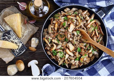 Funghi trifolati or fried porcini sprinkled with parsley in skillet with kitchen towel on old dark wooden table with fresh whole ceps parmesan cheese and olive oil view from above close-up