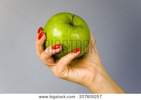 A green apple in a graceful female hand. Background - gradient.