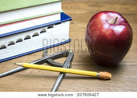Back to school or teacher's appreciation concept with books and red apple on wooden desk.