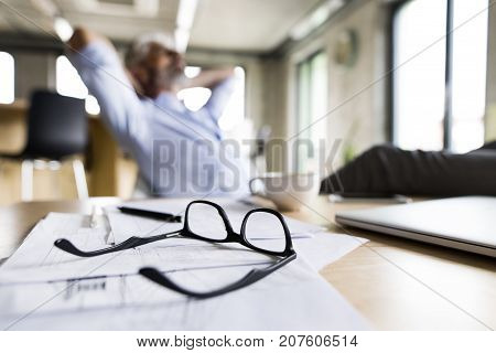 Unrecognizable mature businessman in the office. Eyeglasses and blueprints laid on table.