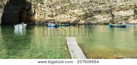 Pleasure boats at the rugged coastline delineated by sheer limestone cliffs and dotted with deep caves on Malta. The Inland Sea is a lagoon of seawater on the island of Gozo linked to the Mediterranean Sea through an opening formed by a narrow natural arc