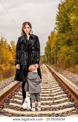 family mother with her son on the forest railway tracks a sense of oppression and danger