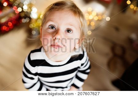 Cute little girl in striped dress, crumbs around her mouth. Christmas season.