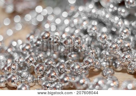 Abstract silver christmas background with soft focus. Thread with beads with golden glare is lying randomly on wooden table and beautiful bokeh.
