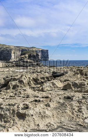 Gozo is a small island of the Maltese archipelago in the Mediterranean Sea. Rugged coastline delineated by sheer limestone cliffs and dotted with deep caves