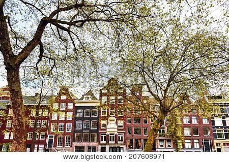 Historic buildings in the city of Amsterdam. Typical Dutch brick houses in Holland.