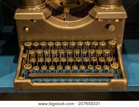 Qwerty keys on ancient mechanical typewriter on blue desk surface