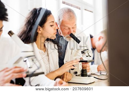 Senior teacher teaching biology to his high school student in laboratory.