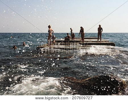 Yalta Crimea - September 20 2017: breakwater with swimmers and sunbathers people