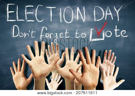 Many waving hands on chalkboard background with text. Election day concept