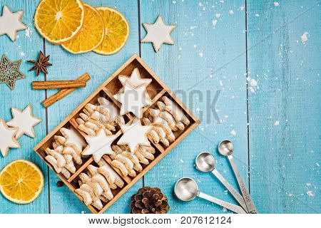Traditional German Star Cookies in a gift box with spices and dried oranges over a light blue background. Christmas or Yom Kippur.