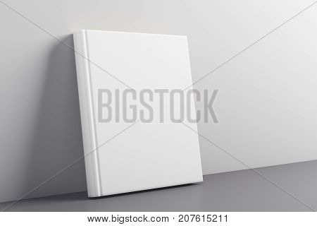 Empty closed white hardcover notepad leaning on concrete wall. Advert concept. Mock up 3D Rendering