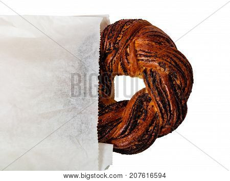 Braided poppy seed round loaf in paper bag isolated on white background