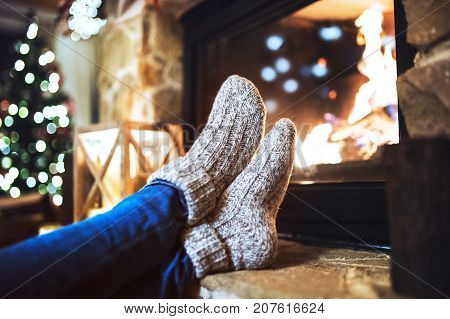 Feet of unrecognizable woman sitting in front of the fireplace, resting. Christmas time.