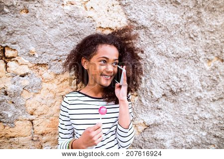 Beautiful african american girl with curly hair outdoors against concrete wall, holding smart phone, making phone call and eating lollipop.