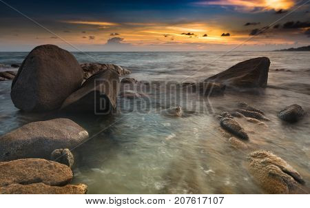 The rock and the sea in the color of sunset time photo with outdoor low and dark lighting seascape.