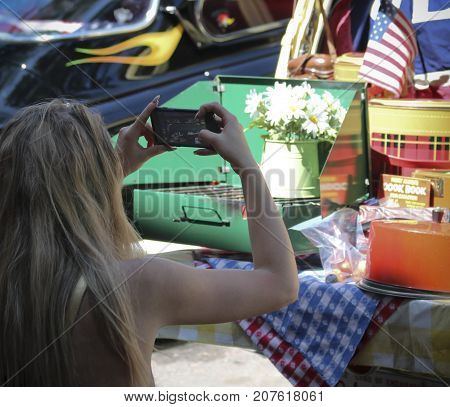 SANTA FE, NEW MEXICO, JULY 4. The Plaza on July 4, 2017, in Santa Fe, New Mexico. A Woman Photographs a Display at a Vintage Car Show a Tradition on the Fourth of July in Santa Fe in New Mexico.