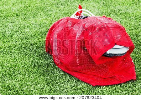 A red practice uniform over full pads is ready to be put on by a high school football player for practice.