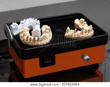Manufacture of molds for dentures in laboratory vibratory table